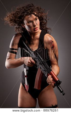 Sexy military, killer woman posing with gun. With dirty face, blood and wound.