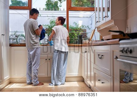 young woman washing dirty dishes together in kitchen