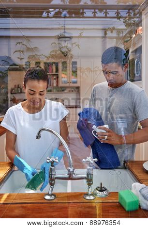 candid image of young woman washing dirty dishes while husband dry off in kitchen