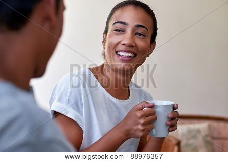 young couple relaxing on sofa couch with morning coffee mug in love