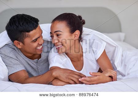romantic young affectionate married couple on bed under duvet at home