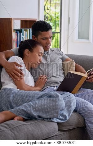 young husband reading literature novel book while wife sleeps in arms on sofa couch in home living room