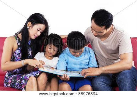 Hispanic Family Read Book On Couch