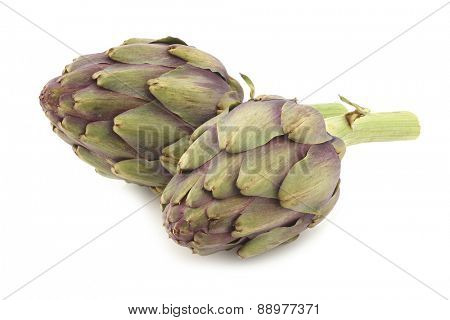 whole artichokes with a stem on a white background