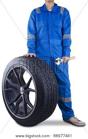 Mechanic Holding A Tire And Wrench