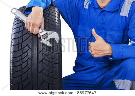 Mechanic With A Tire Showing Thumb Up