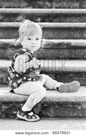 Little Cute Girl In Sitting On The Stairs
