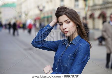 Close up Portrait of a beautiful young woman in a blue jeans shirt on the background of spring street