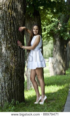 Sexy young woman in white dress in summer park