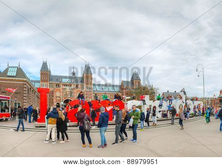 I Amsterdam Slogan With Crowd Of Tourists