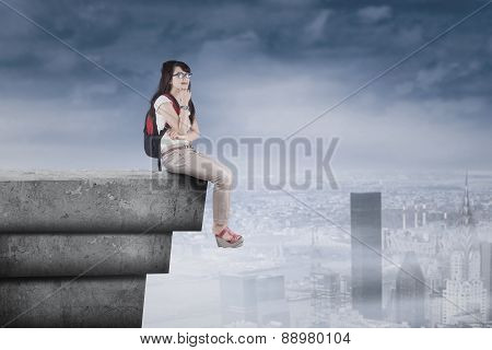 Thoughtful Student Sitting On High Rooftop