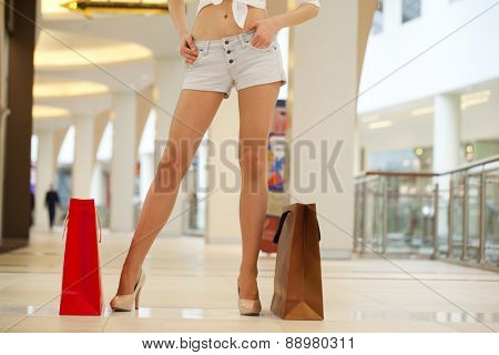 Close up Legs of shopaholic wearing jeans shorts while carrying several paperbags
