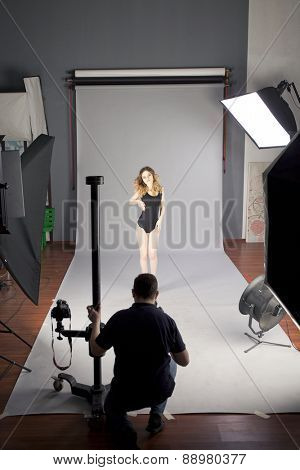 Working conditions in the studio, the photographer photographs the professional model