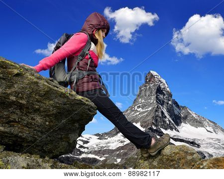 Girl on rock, in the background mount Matterhorn - Swiss Alps, Europe