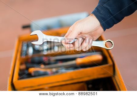 Mechanic's hand holding a wrench