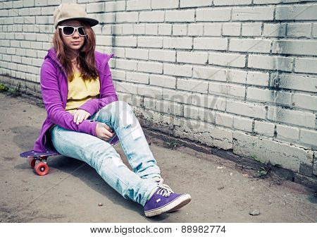 Girl In Jeans And Sunglasses Sits On Skateboard