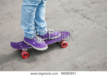 Riding Skateboarder Feet In Blue Jeans And Gumshoes