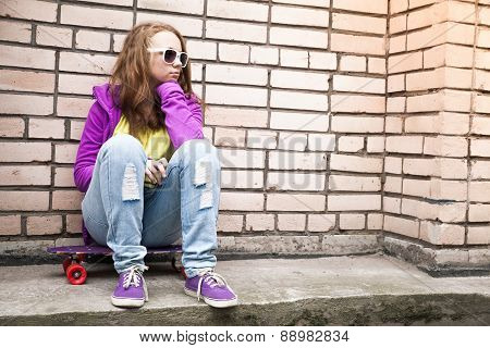Blond Girl In A Sunglasses Sits On Her Skateboard