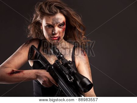 Riot girl with sniper gun close up portrait. With blood and wound on face.