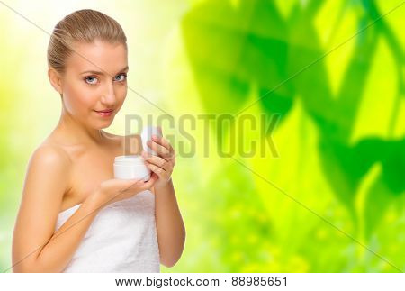 Healthy woman with body cream on floral background