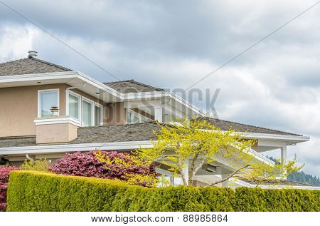 The roof of the house with nice window and rocky outdoor landscape.
