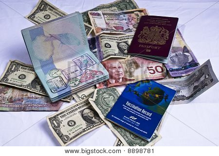 One Open And One Closed United Kingdom Passport And Vaccination Books Laying On Foriegn Currency