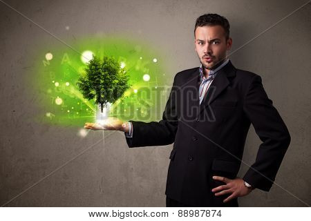 Young businessman holding a glowing tree in his hand