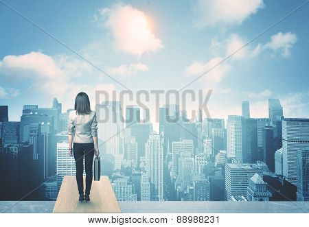 Businesswoman standing on a roof and looking at future city
