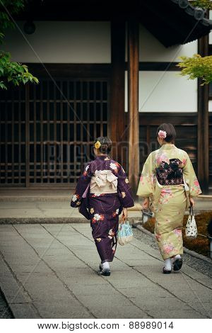 Japanese woman in traditional costume in shrine with historical building in Kyoto, Japan.