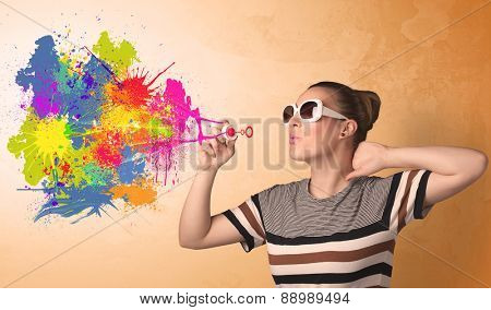 Cute girl blowing bubble spalsh graffiti into wall
