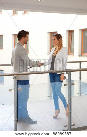 Partners meeting and shaking hands in corridor of apartment house.