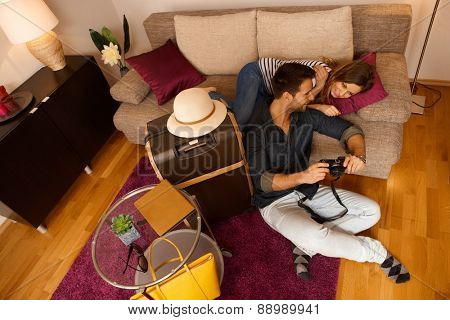 Happy young couple reviewing photos of holiday before leaving apartment. Above view.