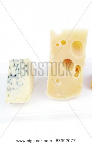 aged parmesan roquefort and gruyere chops delicatessen cheeses on white plate isolated over white background