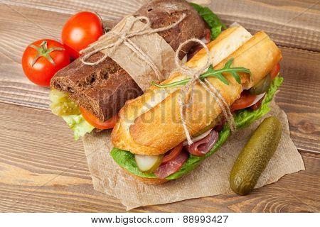 Two sandwiches with salad, ham, cheese and tomatoes on wooden table