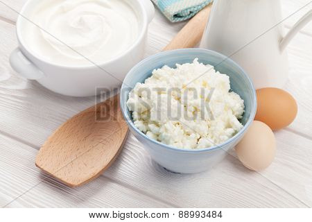 Dairy products on wooden table. Sour cream, milk and cheese