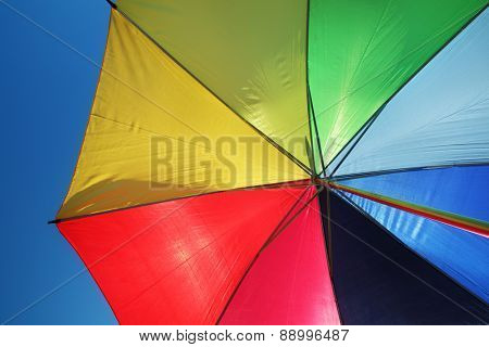Rainbow umbrella and blue sky background