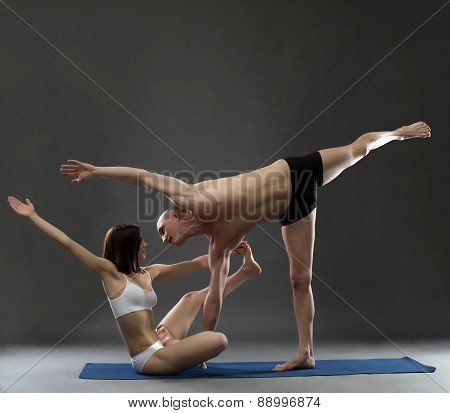 Paired yoga. Instructors posing in complex asana