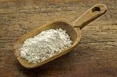 picture of quinoa  - gluten free quinoa flour on a wooden scoop against weathered wood - JPG