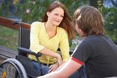 stock photo of disabled person  - girl on a wheelchair is talking to a boy in the park - JPG