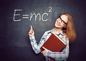 stock photo of formulas  - Happy student girl with book and glasses has written on the blackboard formula in physics - JPG