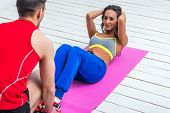 picture of crunch  - athletic sporty couple friends. Woman doing crunches abdominal exercises on floor in gym with a help of guy concept training exercising workout fitness aerobic.