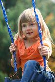 image of swingset  - little girl on swingset outdoors in fall - JPG