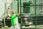stock photo of early-man  - young man play tennis outdoor on tennis field at early morning - JPG