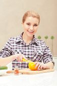 image of yellow-pepper  - Pleasant cooking. Pretty housewife cutting yellow pepper on a slicing board in the kitchen ** Note: Shallow depth of field - JPG