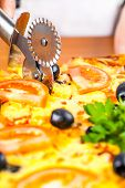stock photo of hot fresh pizza  - chef knife cuts fresh hot vegetable pizza closeup - JPG