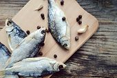 picture of cod  - Salty stockfish cod on wooden board with gaarlic and pepper - JPG