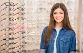 pic of spectacles  - Portrait of smiling woman is standing in spectacles store - JPG