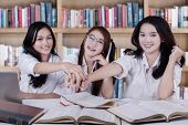 picture of joining hands  - Portrait of three high school students joining hands together in the library - JPG