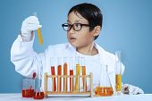 pic of chemical reaction  - Young asian little scientist looking at chemical fluid over blue background - JPG