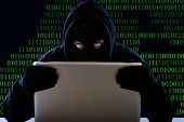 foto of hack  - hacker man in black hood and mask with computer laptop in dangerous dark look hacking system having access to data info and privacy in business digital intruder and cyber crime concept - JPG
